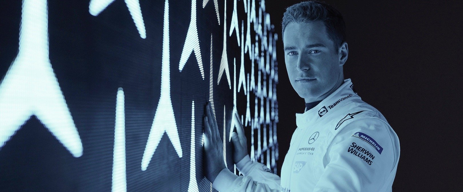 Stoffel Vandoorne in front of a white wall with crossed arms