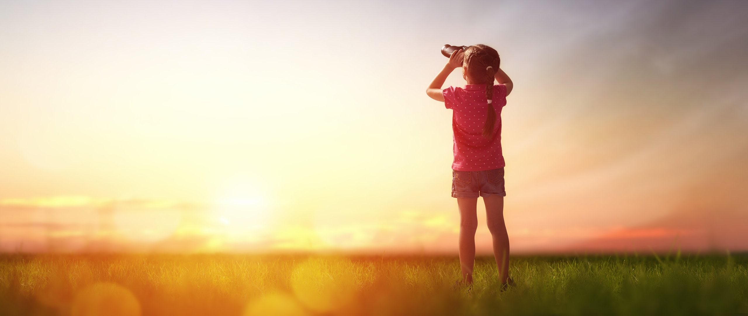 A girl standing on a meadow and looking into the sky with her binoculars.