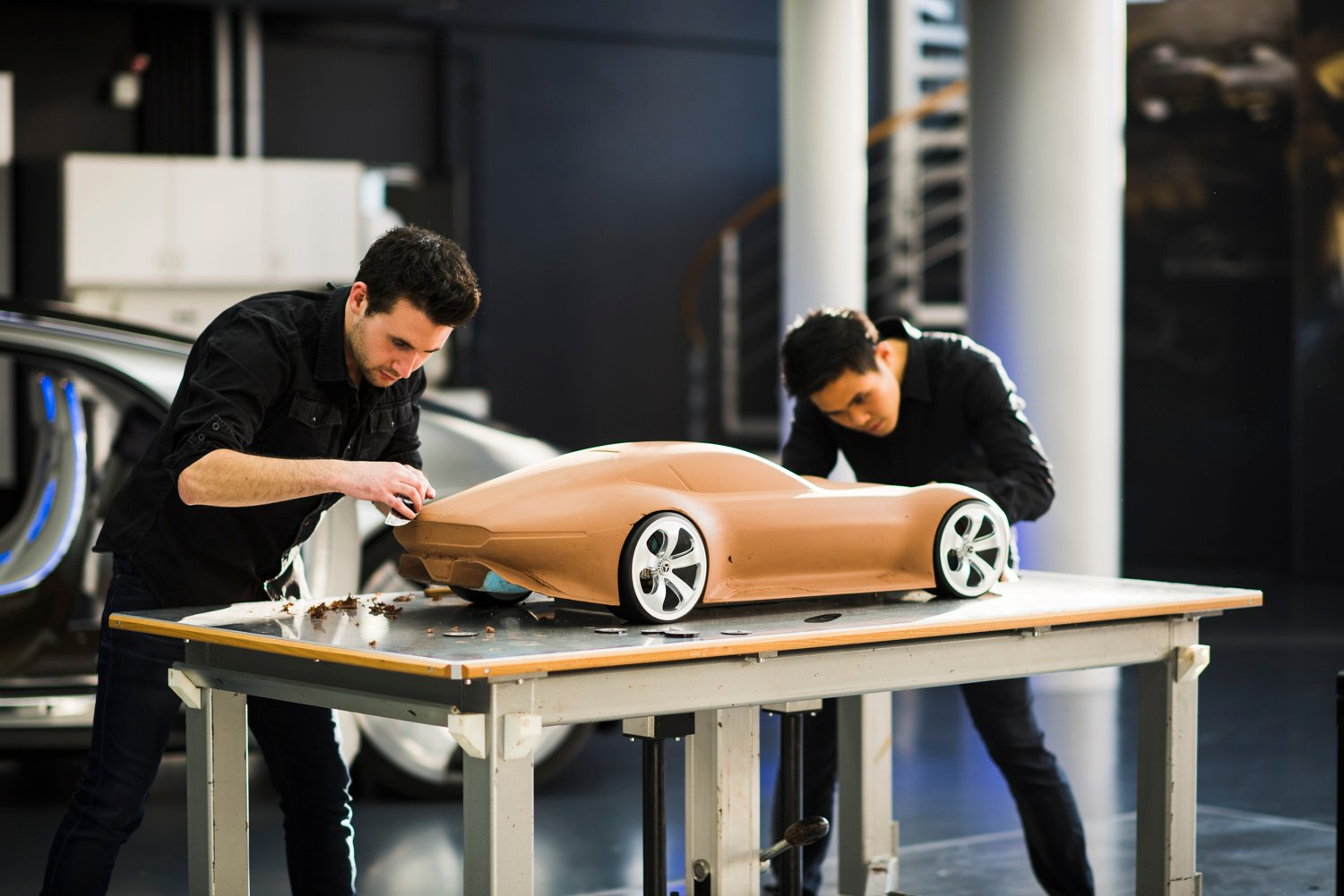 Two designers are working on a 1:4 clay model of a Mercedes-Benz.