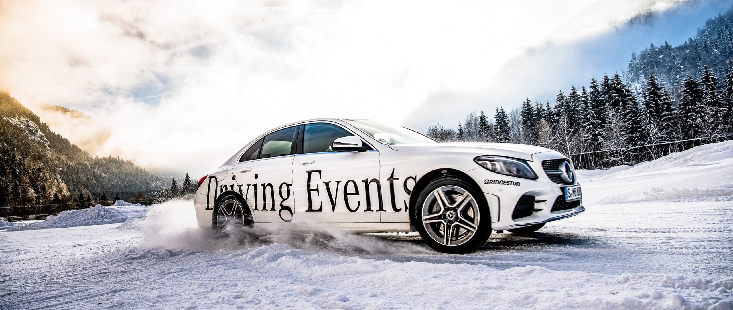 A vehicle is drifting in the snow at a Mercedes-Benz Driving Event.