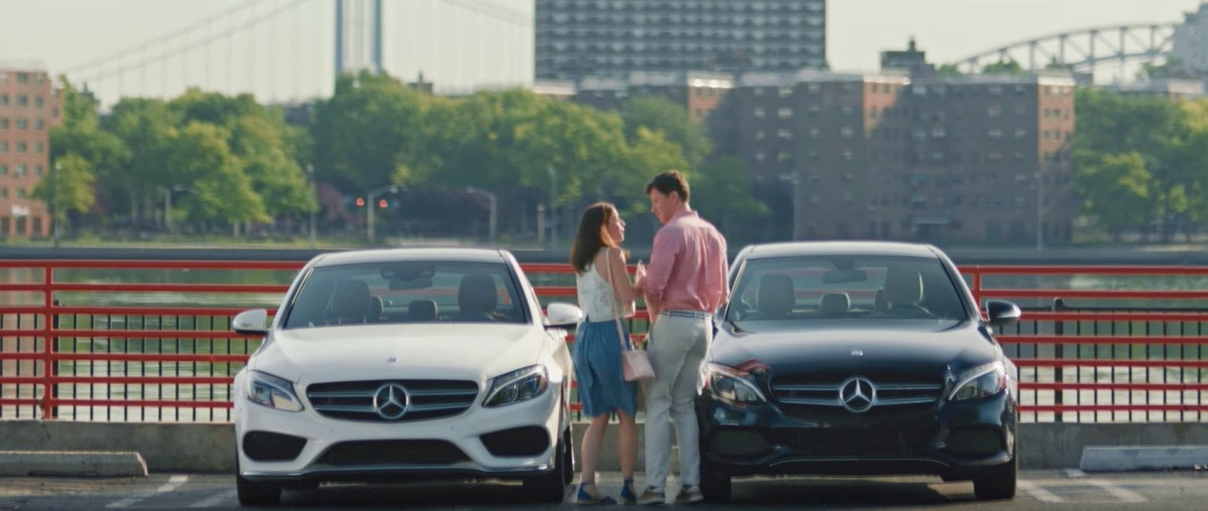 A couple meets in front of their Mercedes-Benz vehicles in a parking lot.