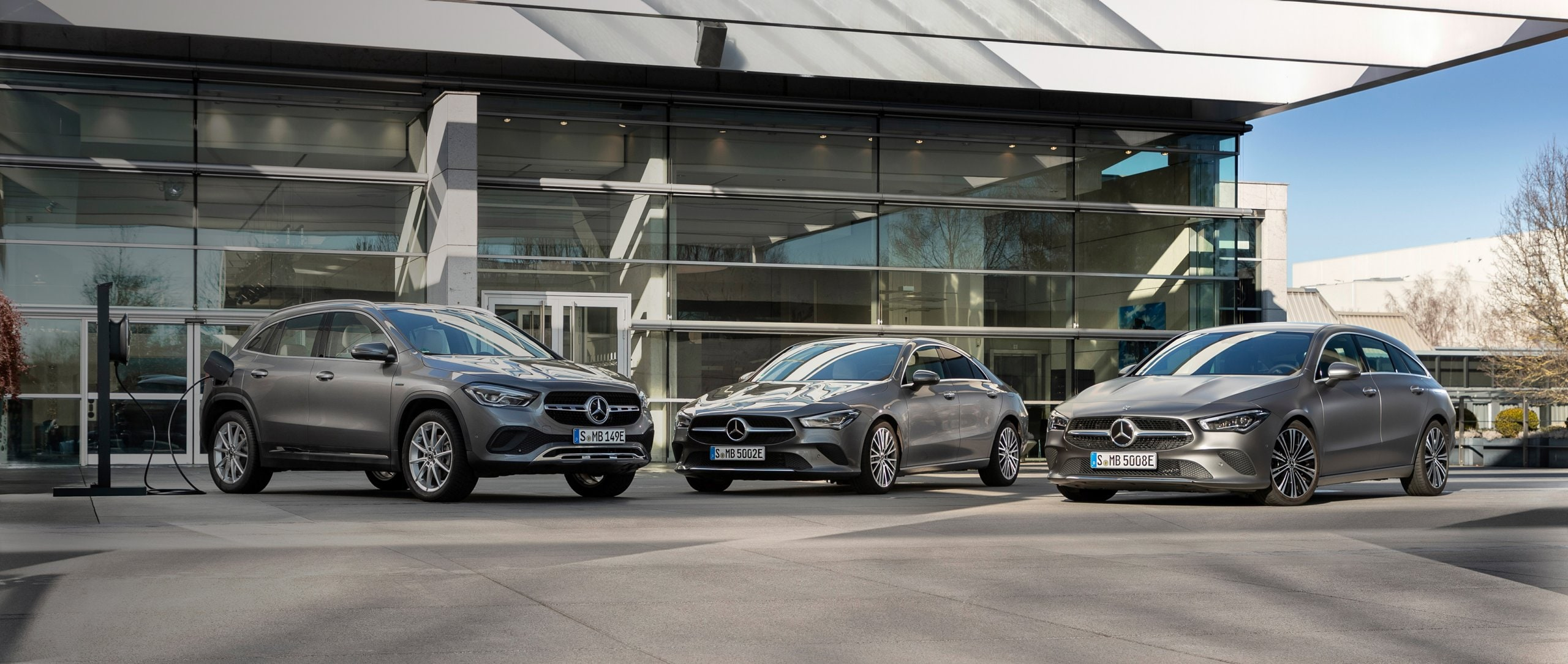 The Mercedes-Benz CLA Coupé, Mercedes-Benz CLA Shooting Brake and Mercedes-Benz GLA stand in front of a building.