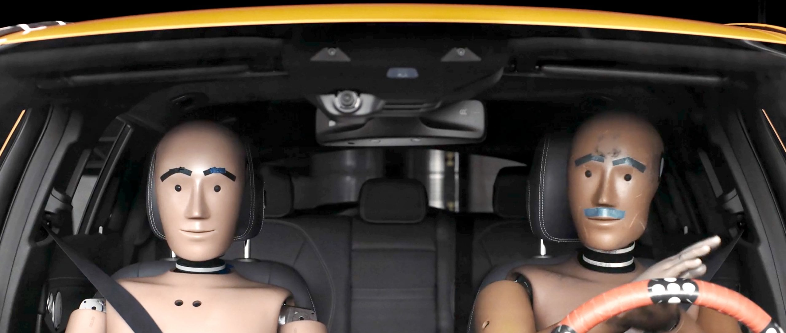 Two test dummies sit in a vehicle and look into the camera.