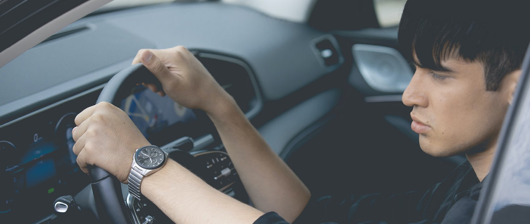Close-up of a Mercedes-Benz automatic watch on the wrist of a person driving.