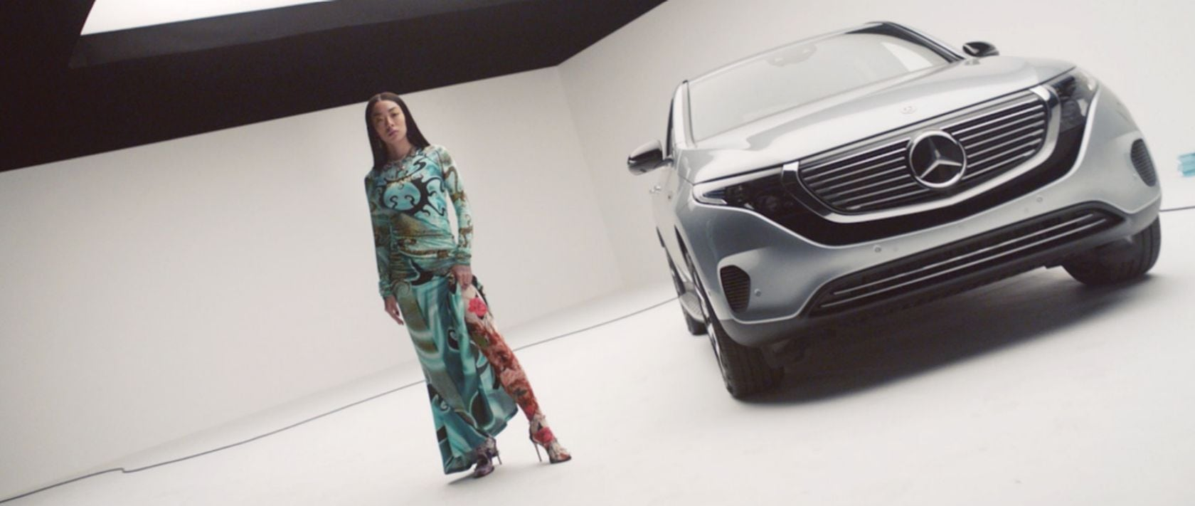 Rina Sawayama standing next to a Mercedes-Benz EQC 400 4MATIC.