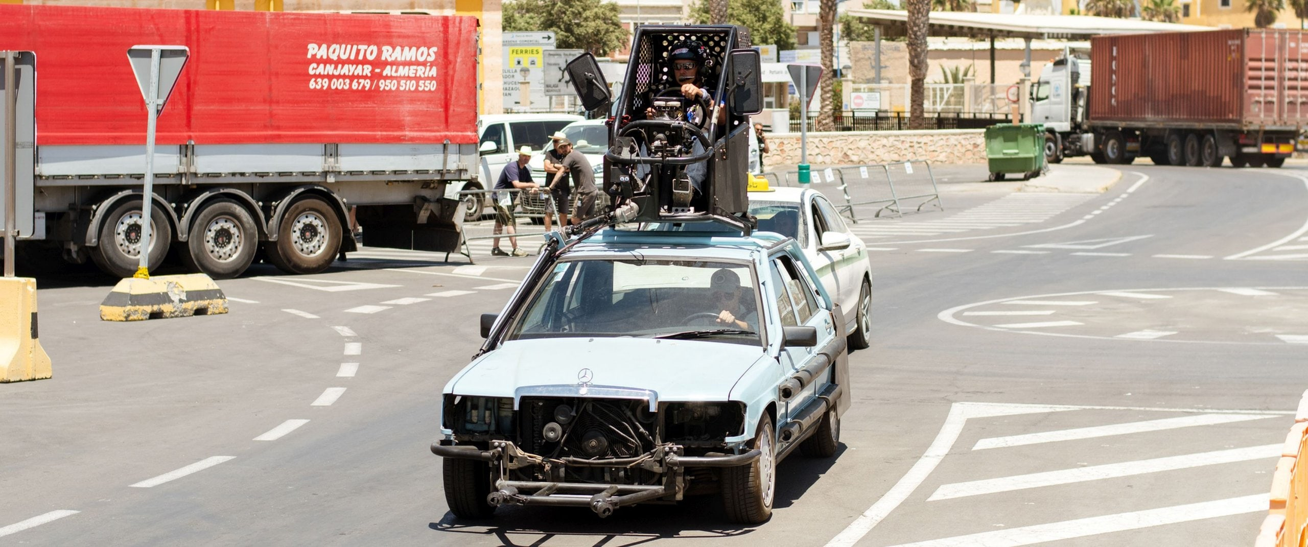 A film car based on a Mercedes-Benz E190 drives through the film set.