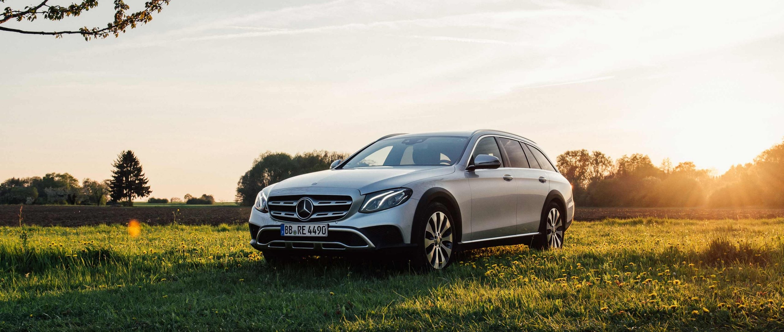 The Mercedes-Benz E-Class All-Terrain (S 213) in the front view on a meadow during a sunset.