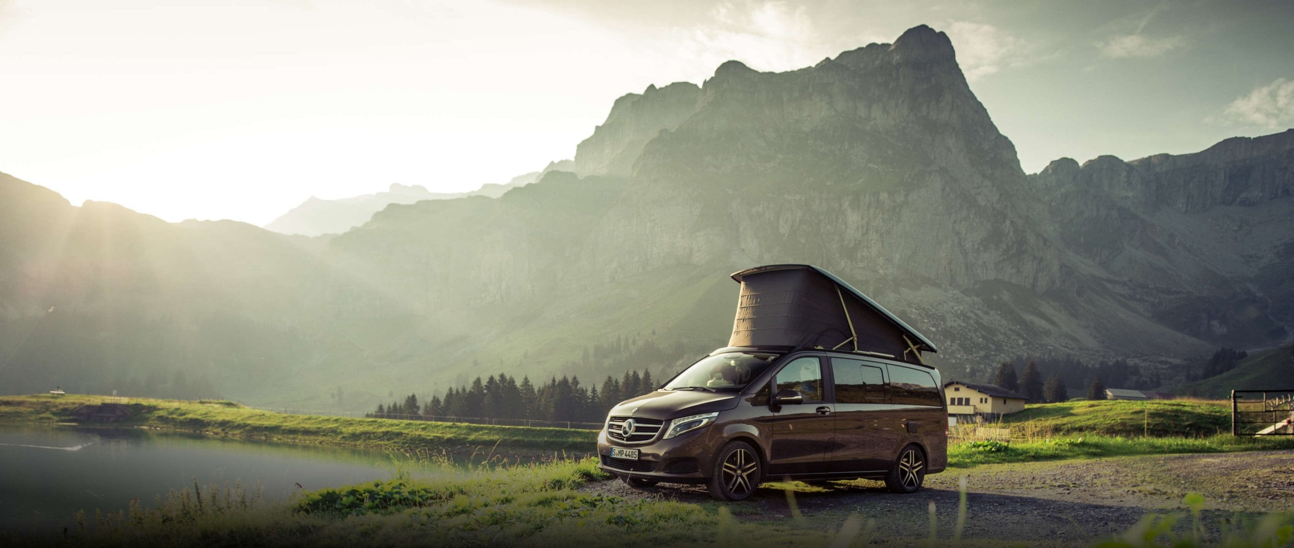 The side view of the Mercedes-Benz Marco Polo (W 447) in dolomite brown metallic near a mountain lake.