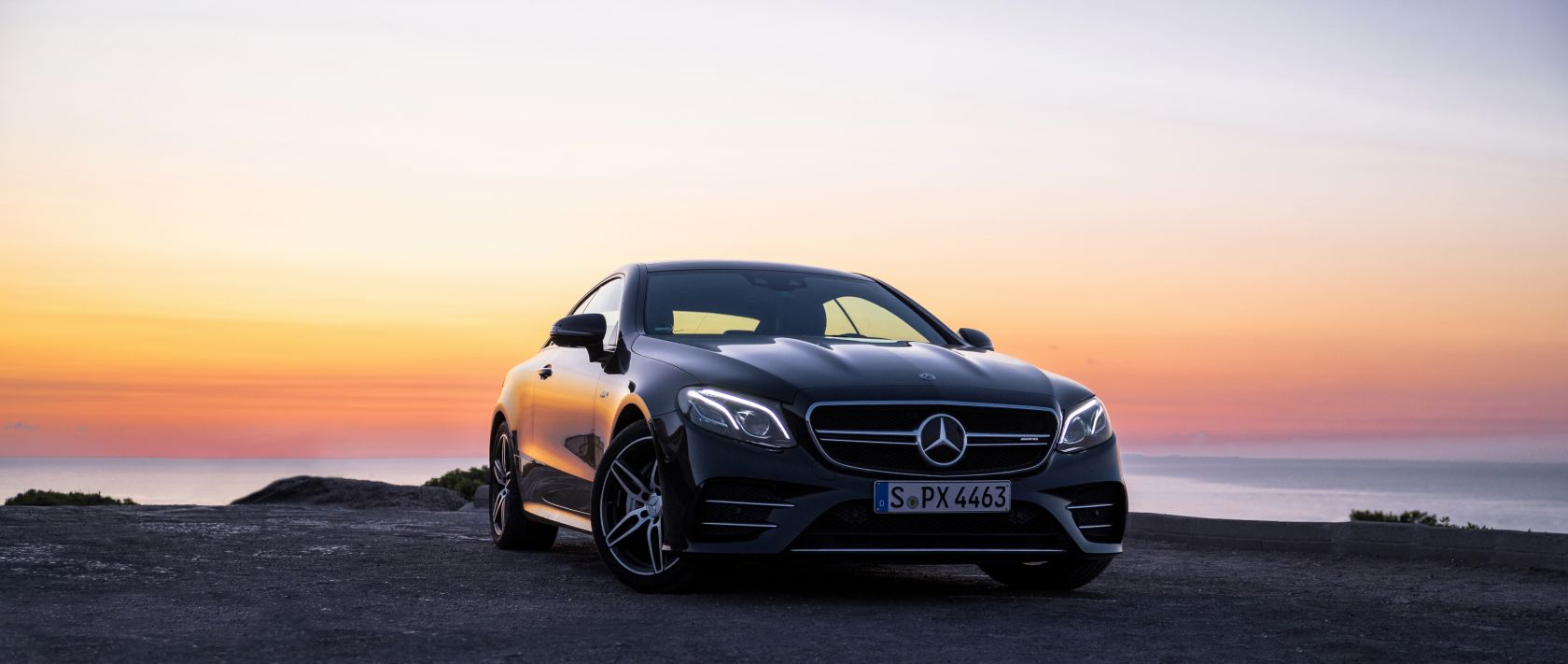 The Mercedes-AMG E 53 4MATIC+ Coupé (C 238) in black in front of a sunset.