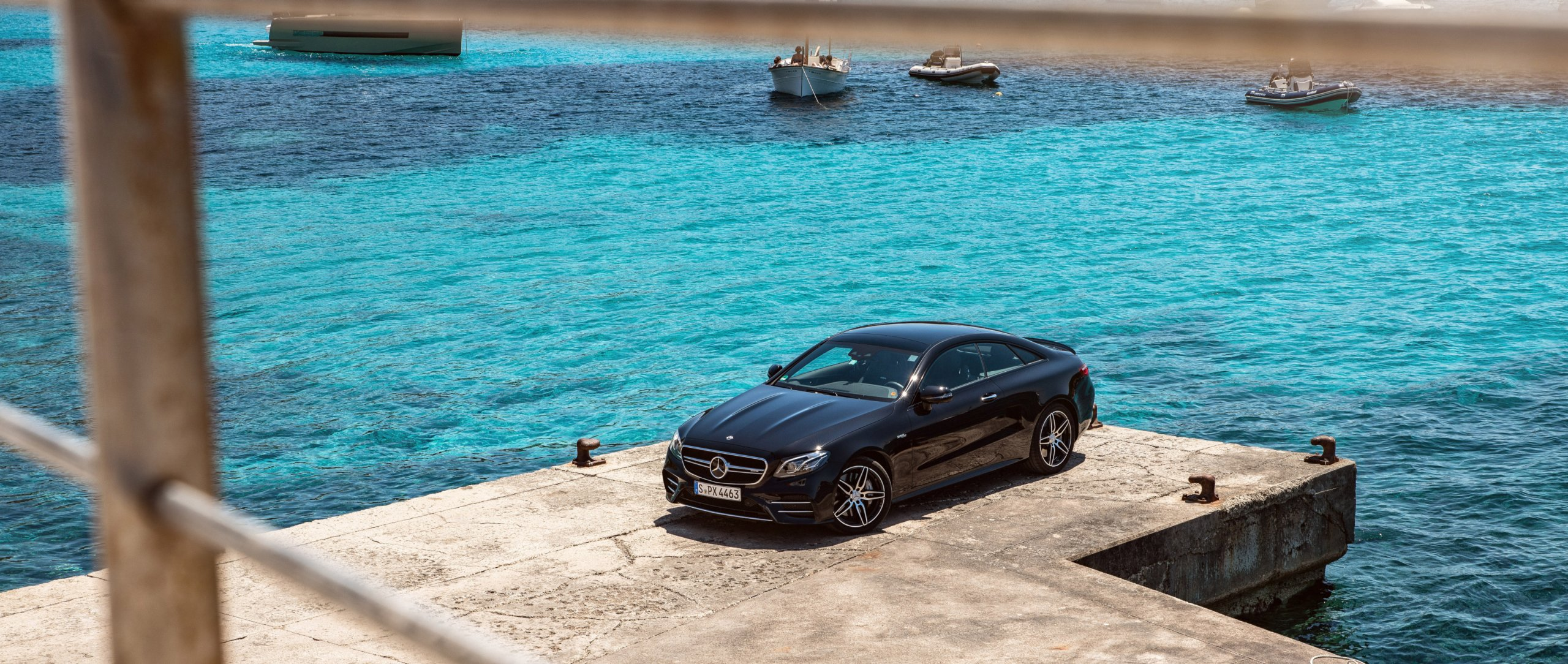 The Mercedes-AMG E 53 4MATIC+ Coupé (C 238) in black at a harbour with ships in the background.