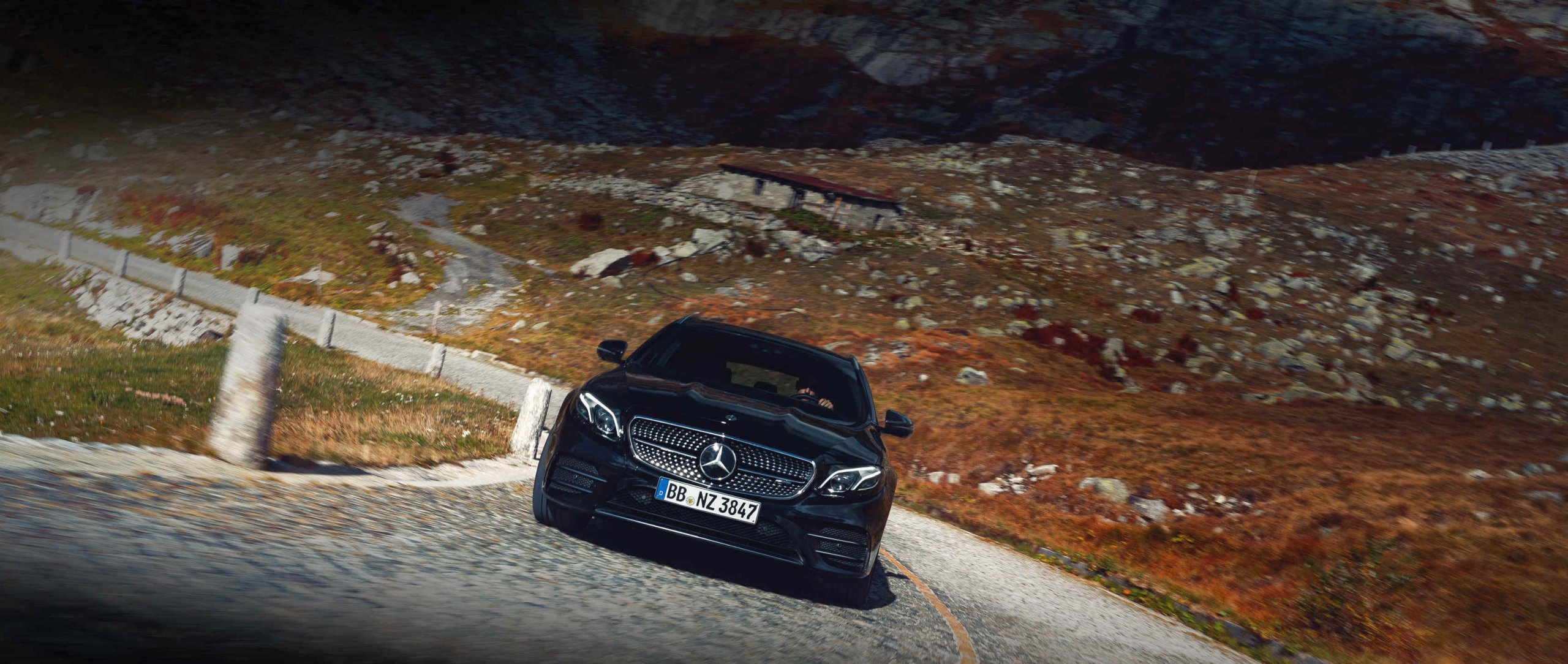 The front view of the Mercedes-AMG E 53 4MATIC+ Estate (S 213) in obsidian black metallic with 19-inch AMG 5-twin-spoke light-alloy wheels on a narrow and winding mountain pass.