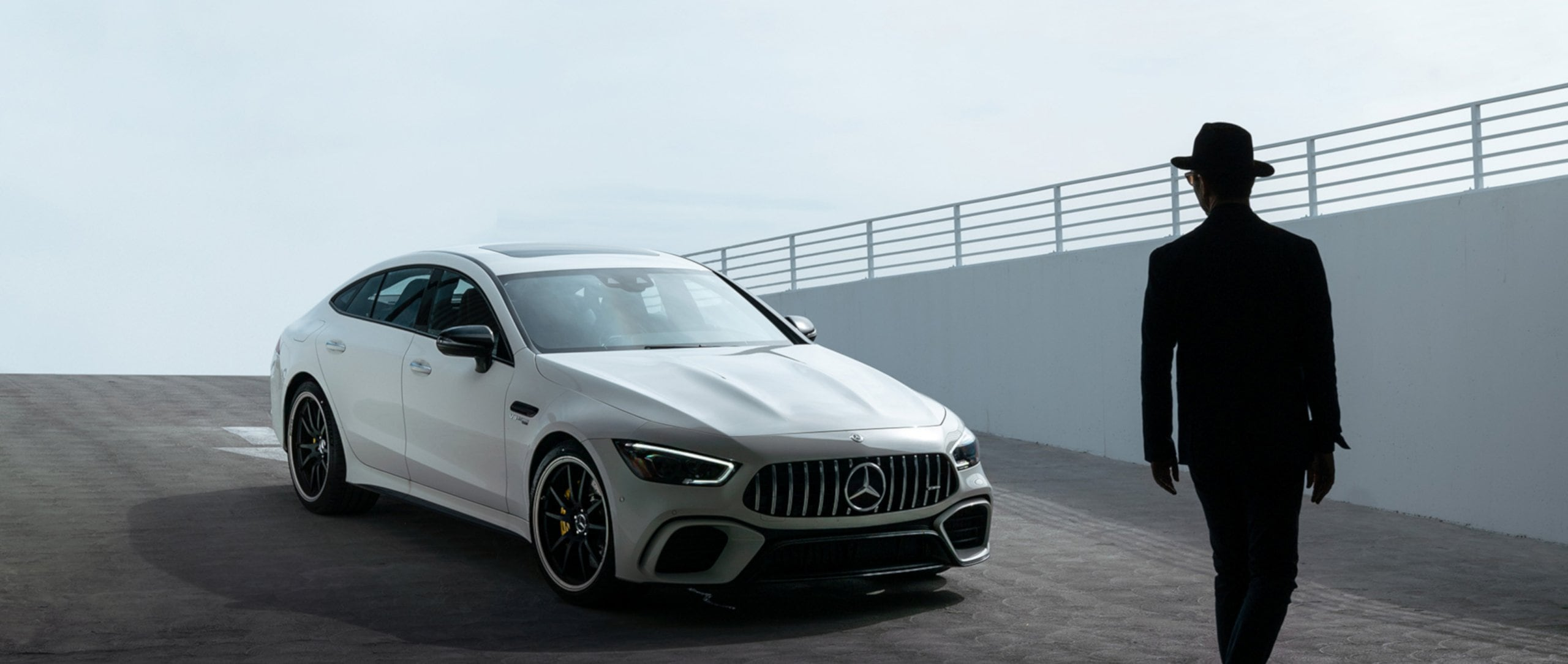 The Mercedes-AMG GT 63 S 4MATIC+ (X 290) in designo diamond white bright with 21-inch AMG 5-twin-spoke forged wheels painted in matt black with a high-sheen rim flange at the entry of an underground car park.
