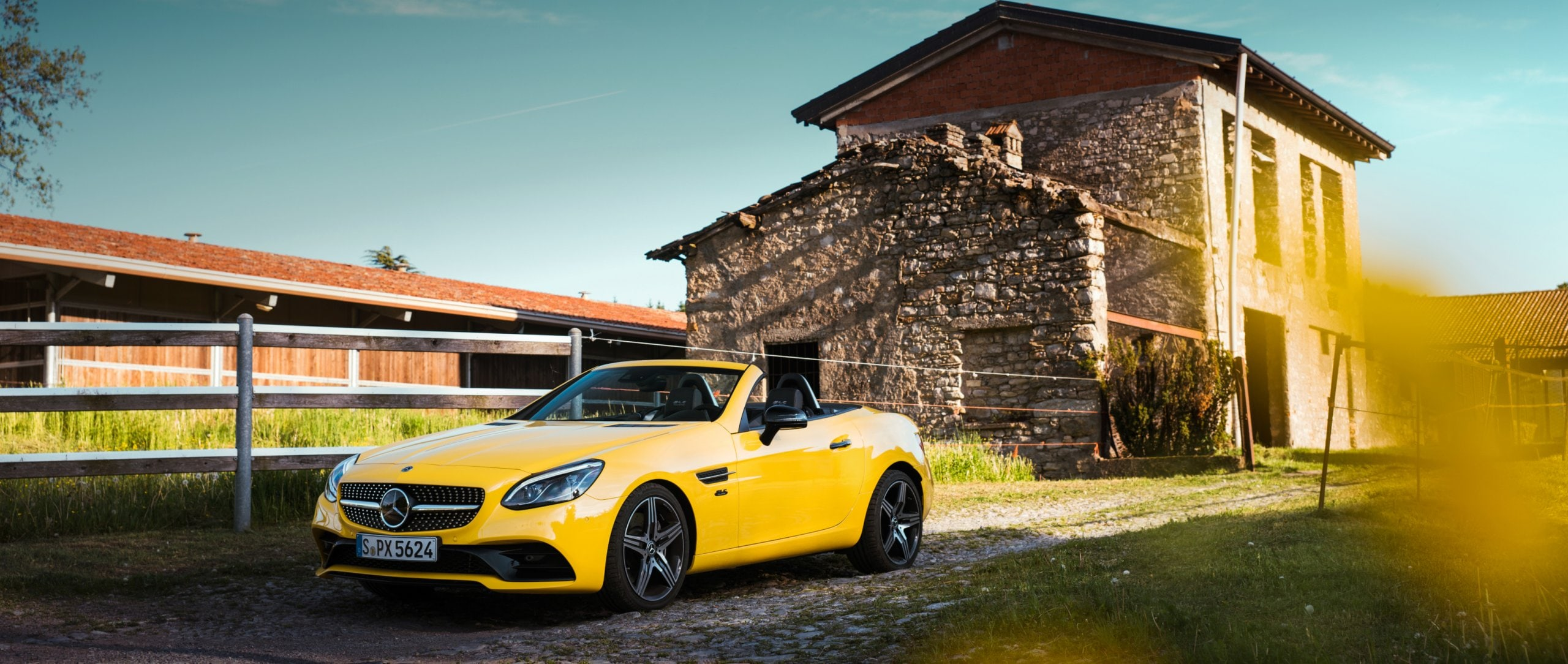 The Mercedes-Benz SLC 300 Final Edition (R 172) in sun yellow with 18-inch AMG 5-spoke light-alloy wheels painted in titanium grey on a farm.