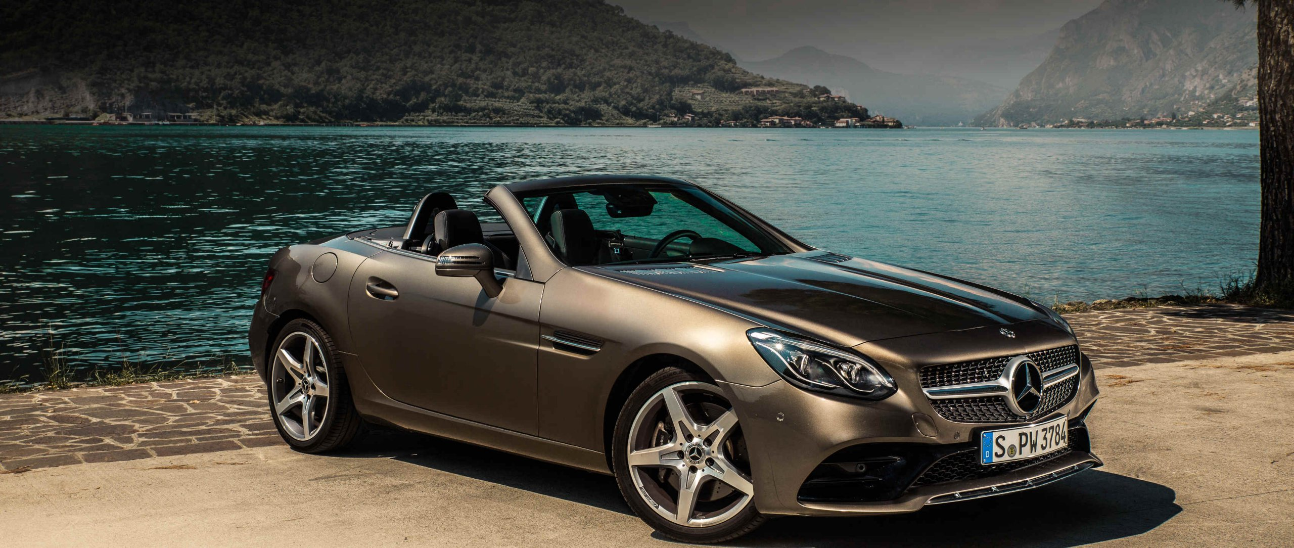 Front view of the Mercedes-Benz SLC 300 Roadster (R 172) in indium grey metallic with 18-inch AMG 5-spoke light-alloy wheels in front of a lake.