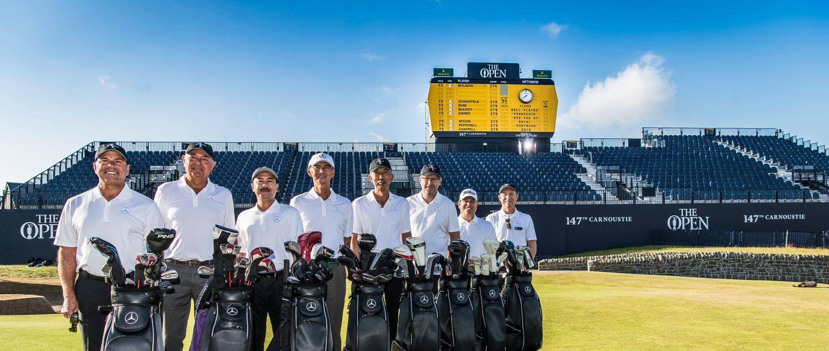 The eight participants of the Monday After Event 2018 stand in front of the iconic The Open leaderboard.