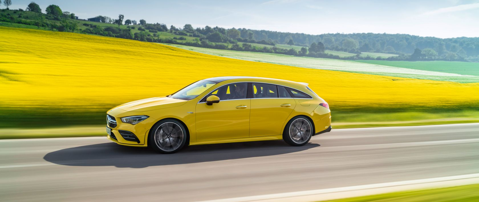 The new 2019 Mercedes-AMG CLA 35 4MATIC Shooting Brake (X 118) in sun yellow passes a rape field.