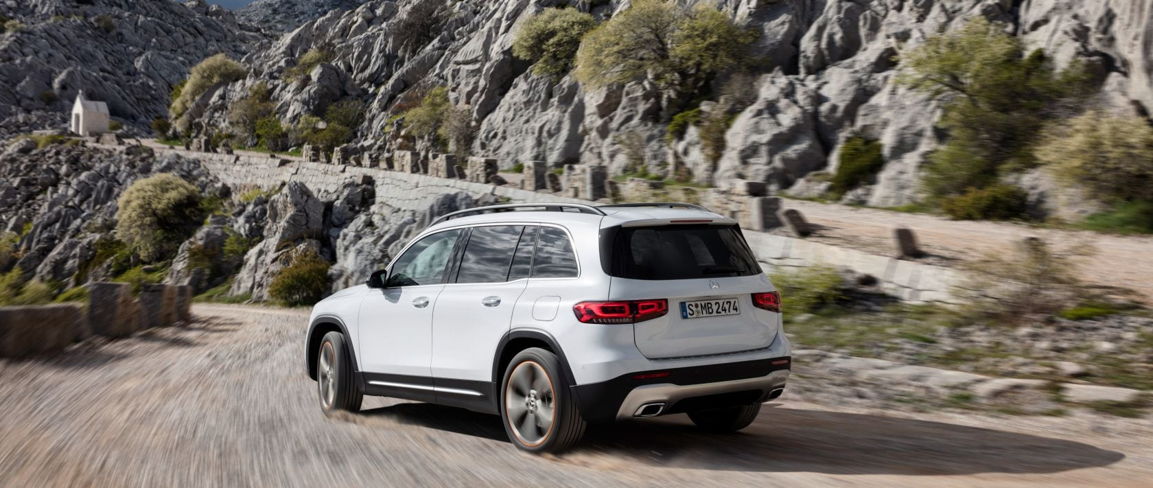 Rear view of the new 2020 Mercedes-Benz GLB (X 247) in polar white on a rough road.