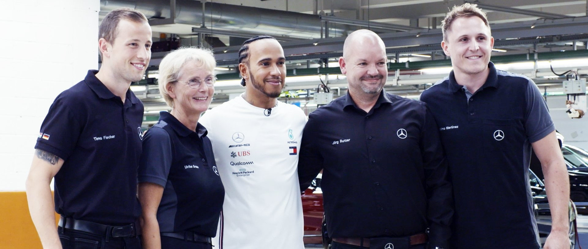 Lewis Hamilton stands with some employees of Mercedes-Benz in the Mercedes-Benz plant Sindelfingen and smiles into the camera.