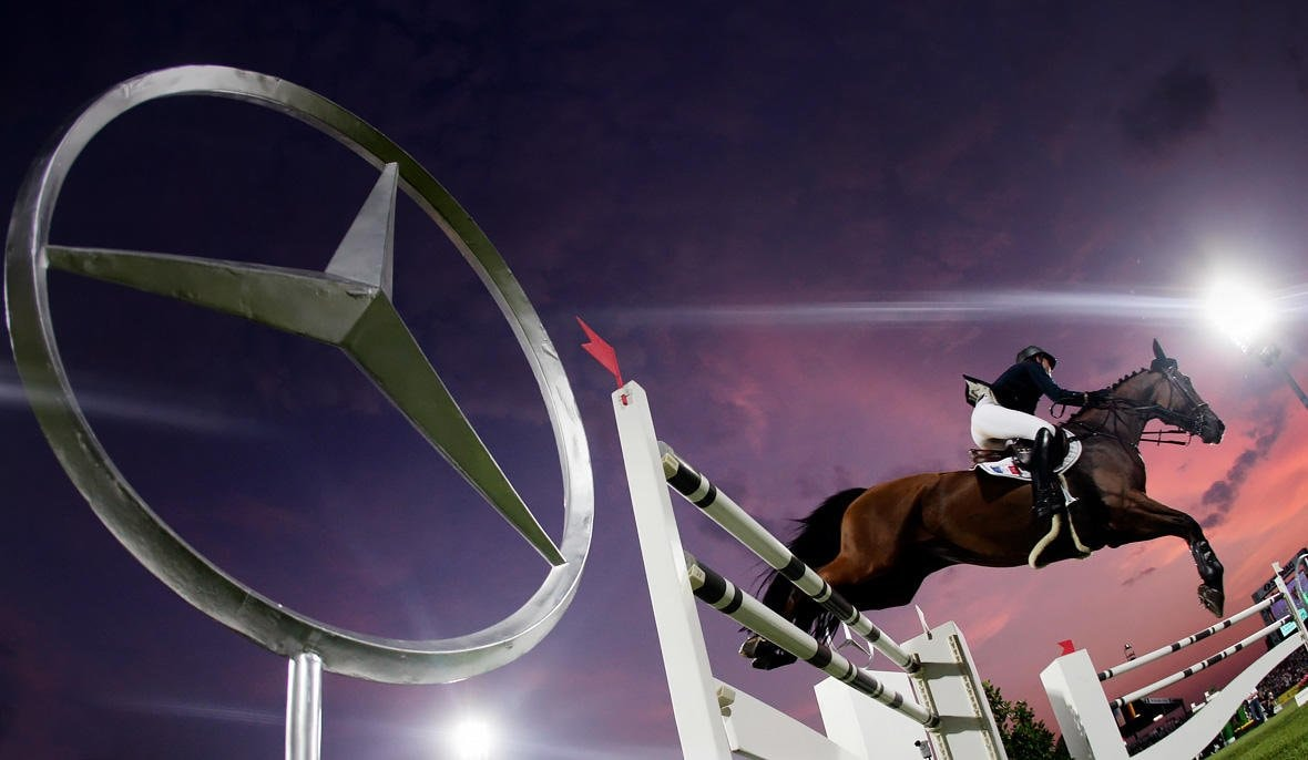 The Mercedes-Benz symbol and a horse rider, jumping over the fence.