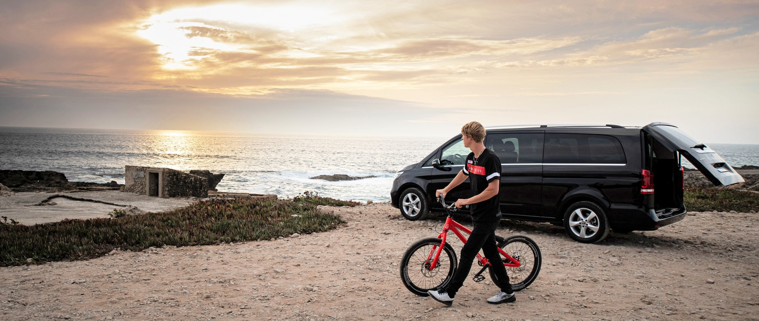 A biker cycling next to a Mercedes-Benz V-Class in the background