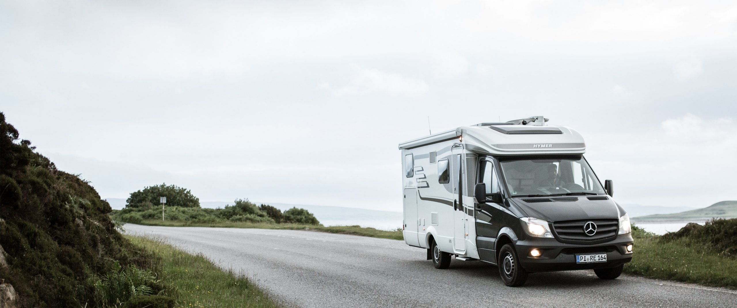 The Hymer motorhome with the Sprinter chassis drives through Scotland´s hilly landscape while dawn is approaching.