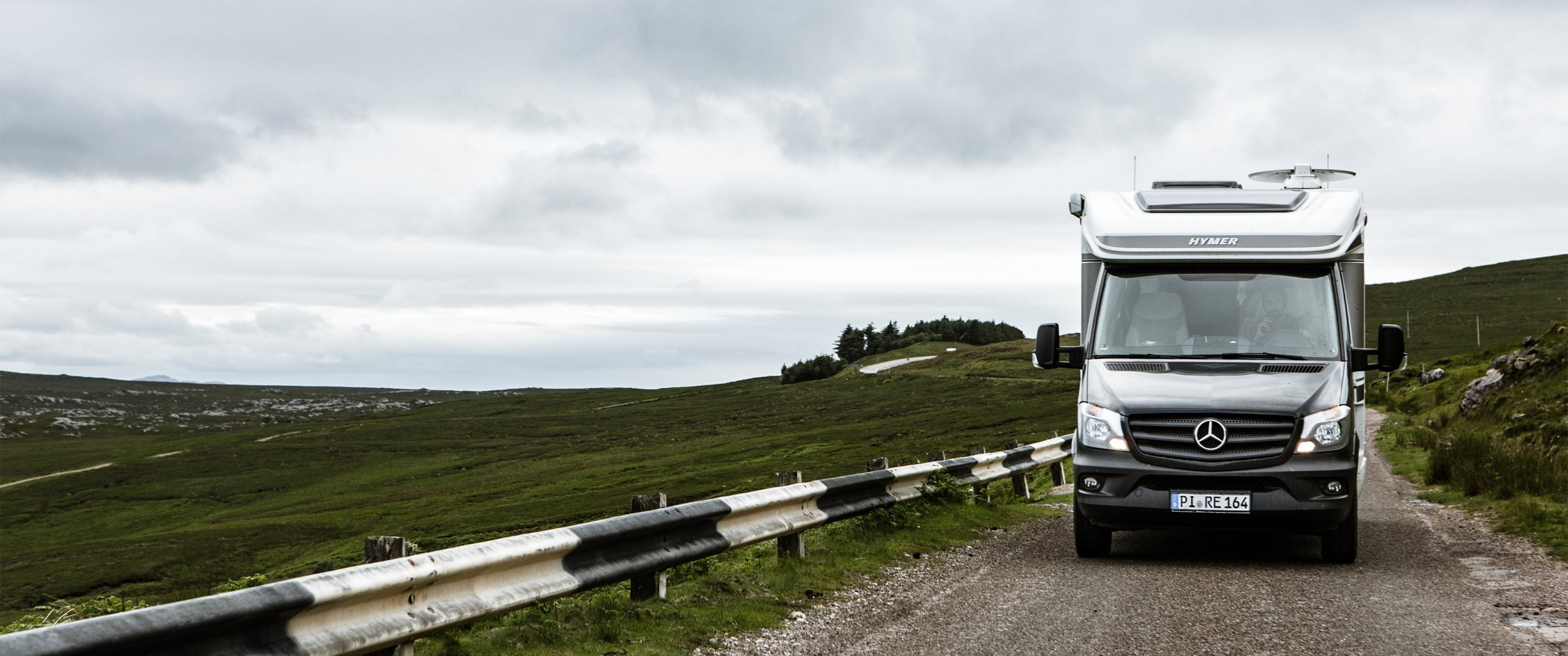 The Hymer motorhome with a Sprinter chassis drives through the green and hilly landscape of Scotland.
