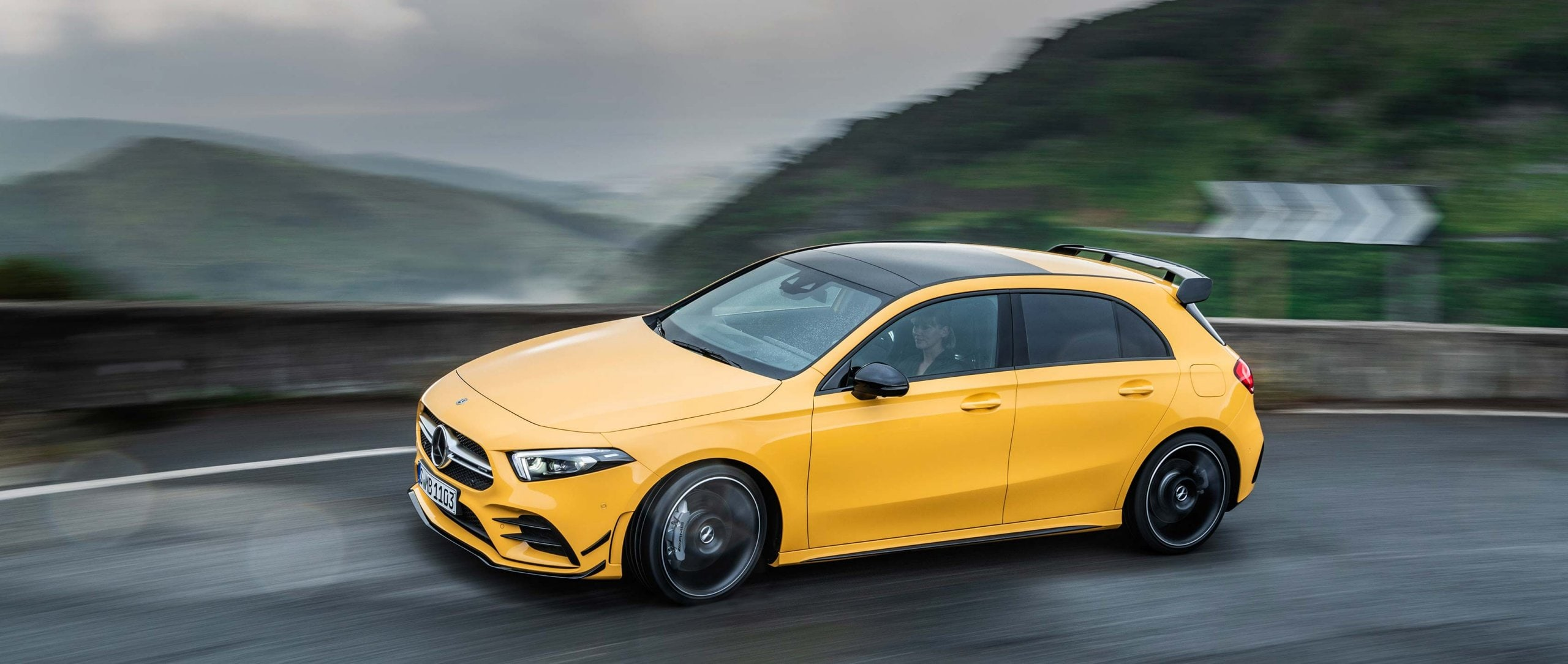 The 2019 Mercedes-AMG A 35 4MATIC (W 177) in sun yellow on a country road in side view.