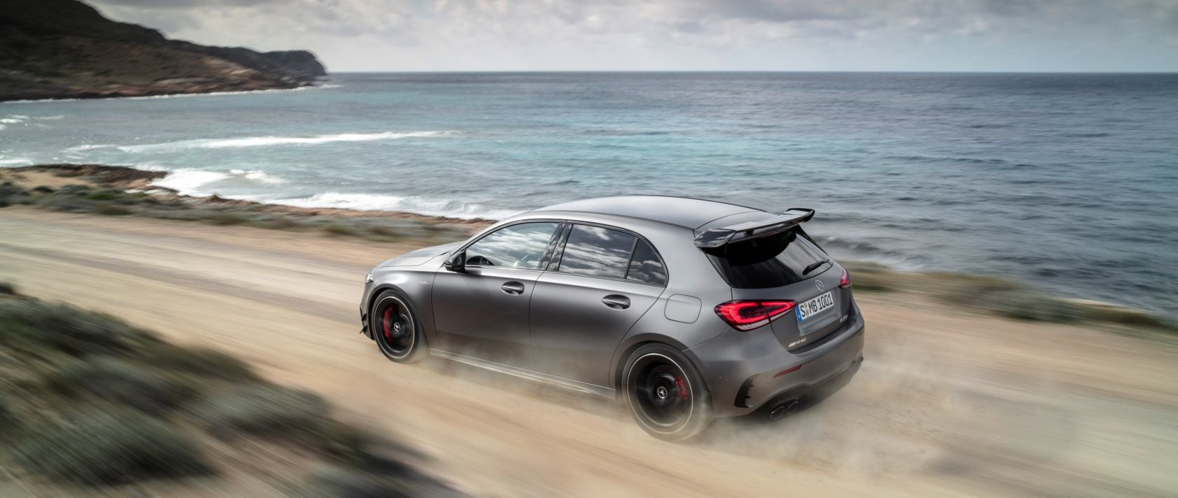 The new 2020 Mercedes-AMG A 45 4MATIC+ (W 177) in designo mountain grey magno: rear view on a dirt road.
