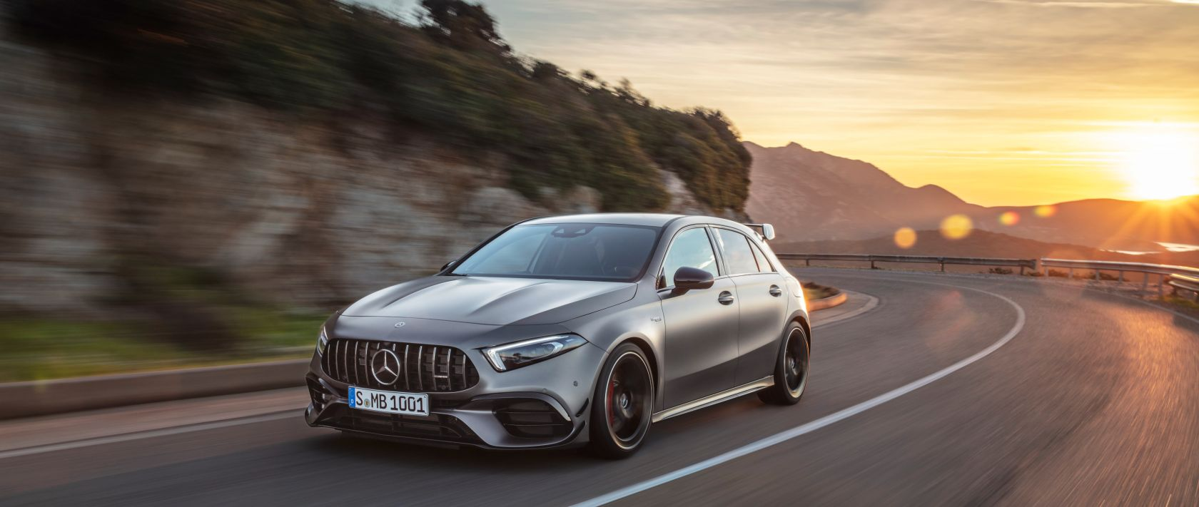 The new 2020 Mercedes-AMG A 45 4MATIC+ (W 177) in designo mountain grey magno on a country road during sunset.