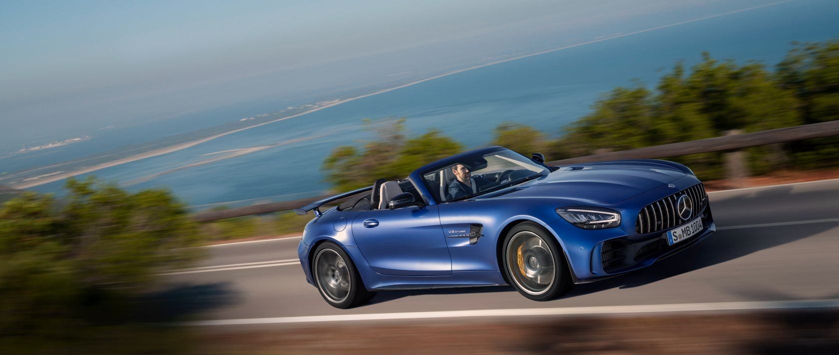 The new Mercedes-AMG GT R Roadster (R 190) in designo brilliant blue magno in side view on a coastal road.