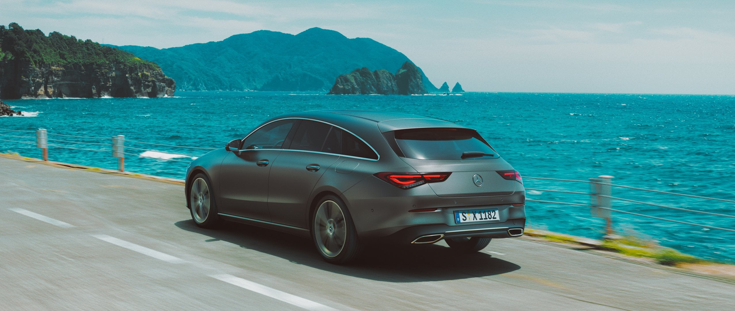 The 2019 Mercedes-Benz CLA Shooting Brake (X 118) in designo Mountain Grey magno on a coastal road.