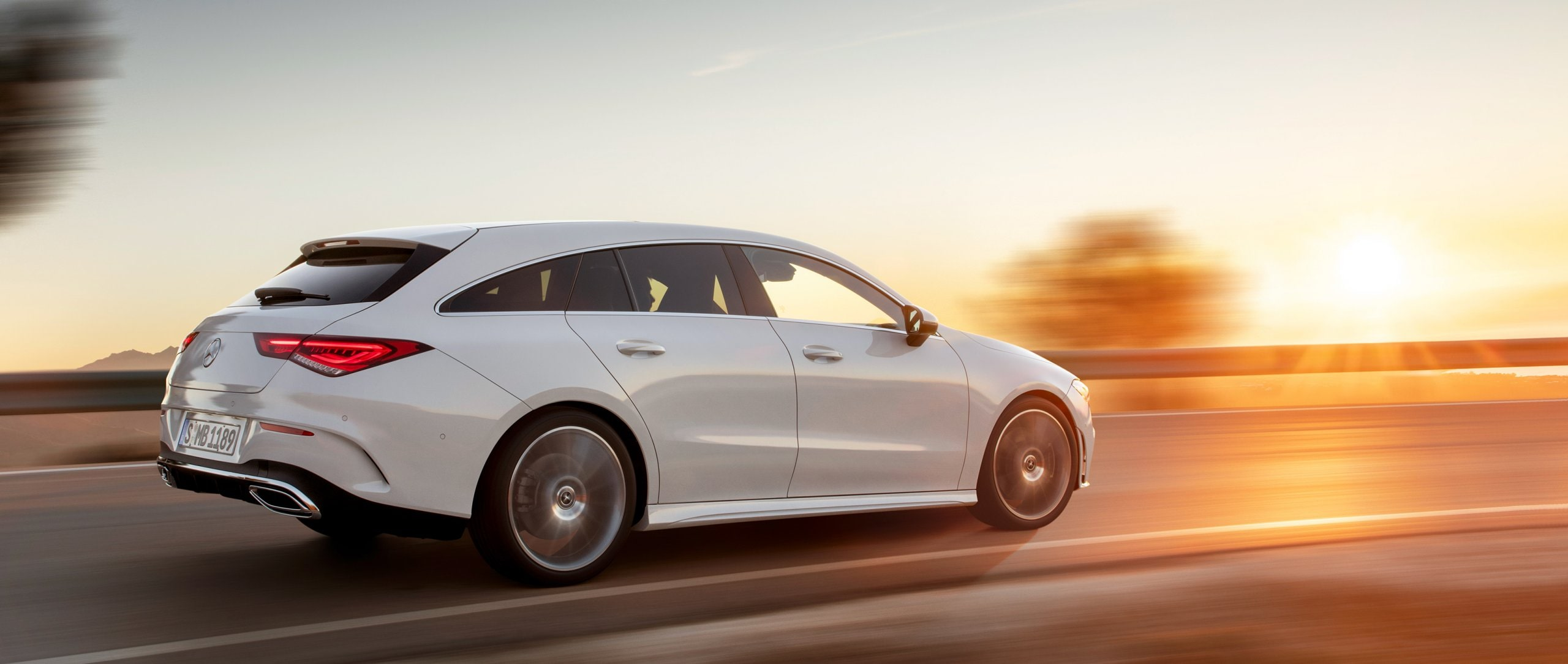 The 2019 CLA Shooting Brake (X 118) with AMG Line in digital white metallic in the side view at sunset.