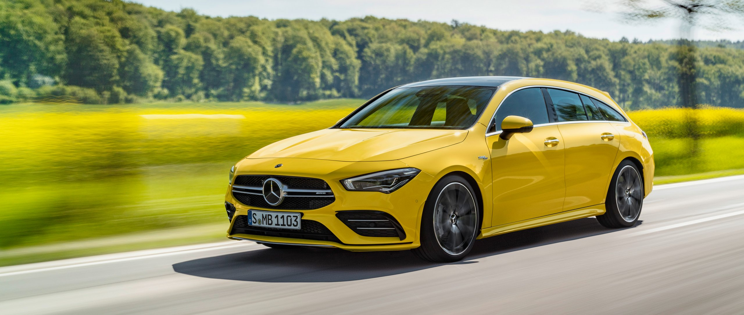 The new 2019 Mercedes-AMG CLA 35 4MATIC Shooting Brake (X 118) in sun yellow in side view on a country road.