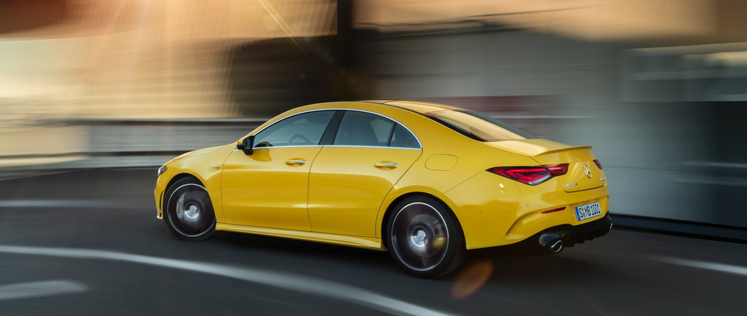 Rear view of the new 2019 Mercedes-AMG CLA 35 4MATIC (C 118) in sun yellow driving on the street.