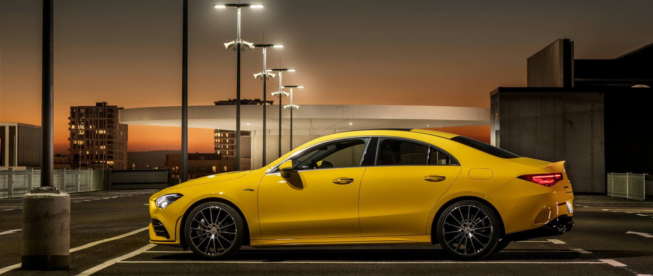 The new 2019 Mercedes-AMG CLA 35 4MATIC (C 118) in sun yellow on top of a parking garage.