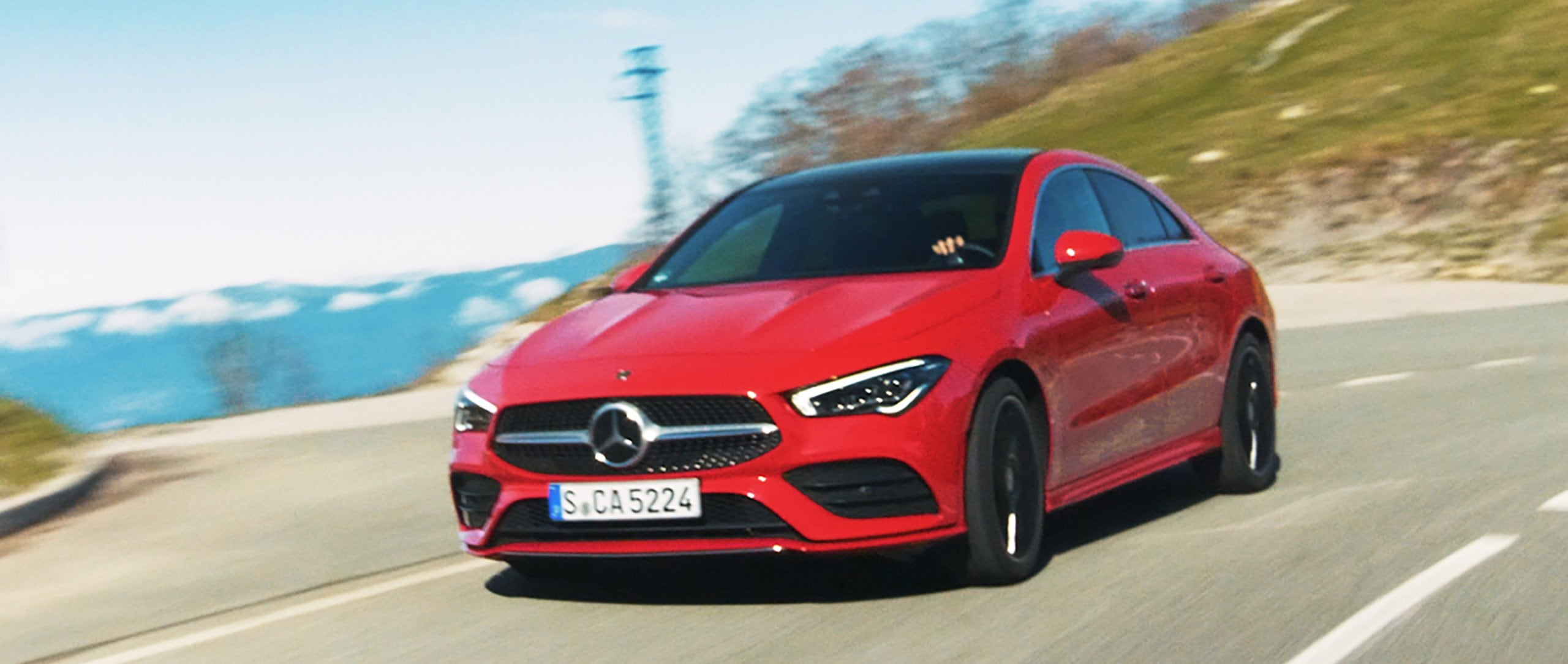 The new 2019 Mercedes-Benz CLA 250 4MATIC Coupé (C 118) in jupiter red driving on a country road.