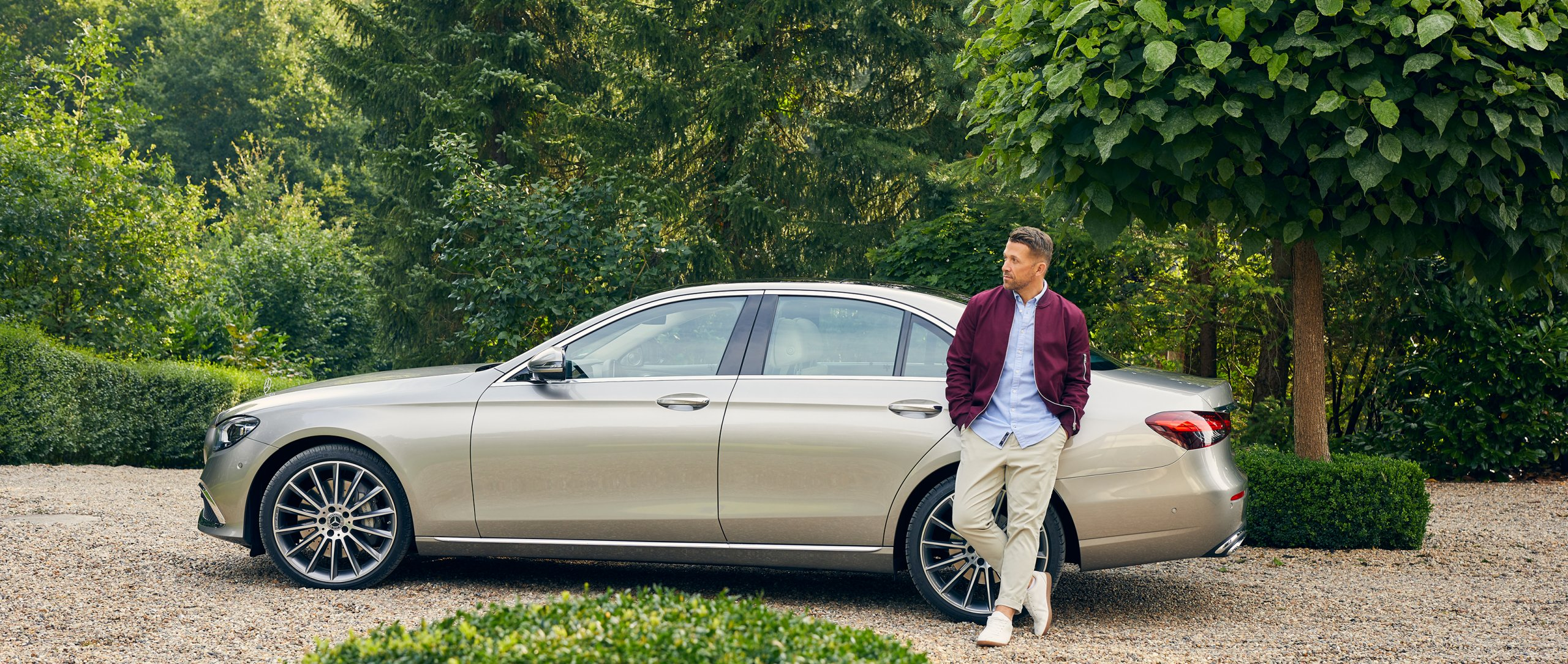 Florian Ambrosius standing in front of the new Mercedes-Benz E-Class.