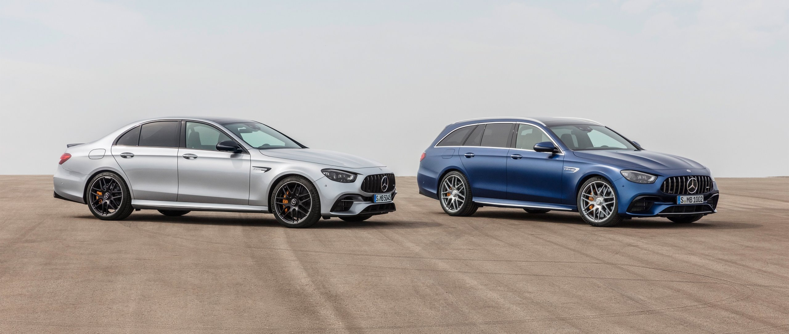 The Mercedes-AMG E 63 4MATIC+ Saloon and Estate standing side by side on a street.