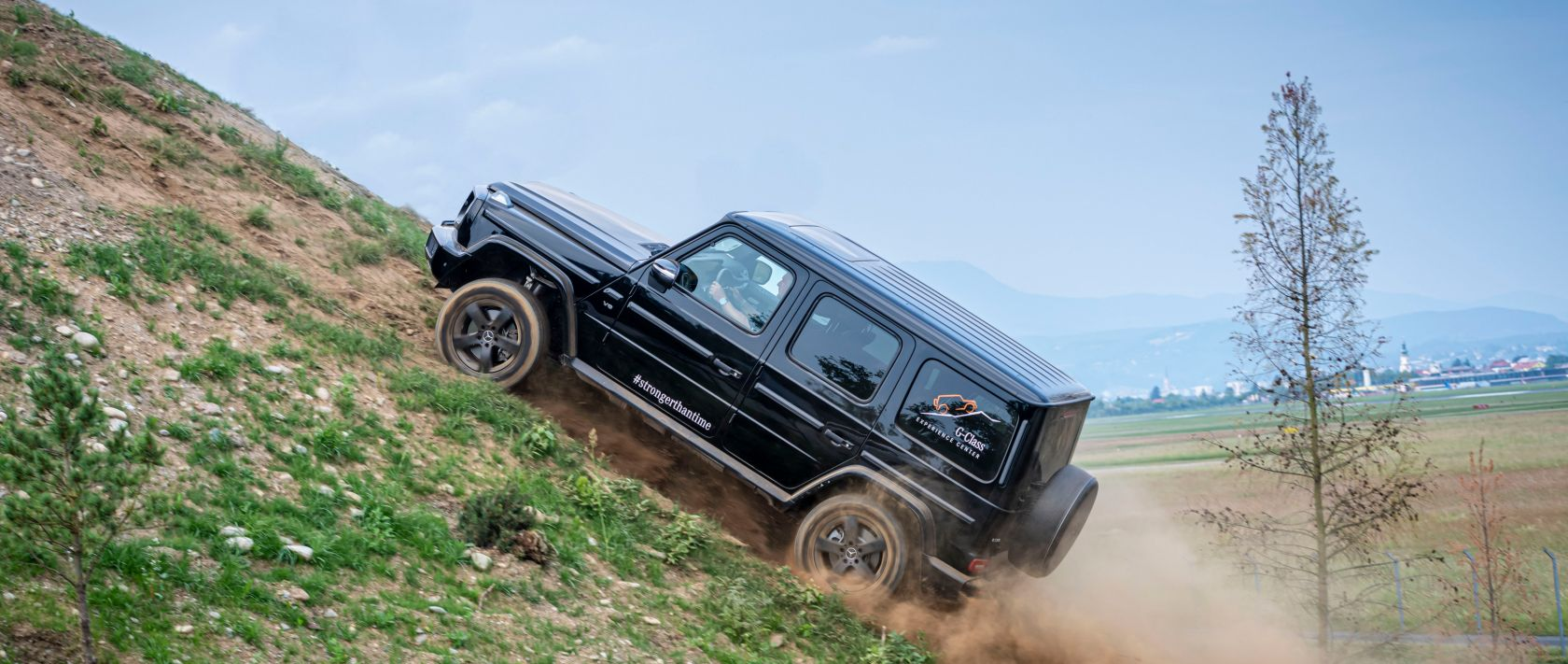 The Mercedes-Benz G 500 (W 463) in obsidian black metallic climbs a hill.