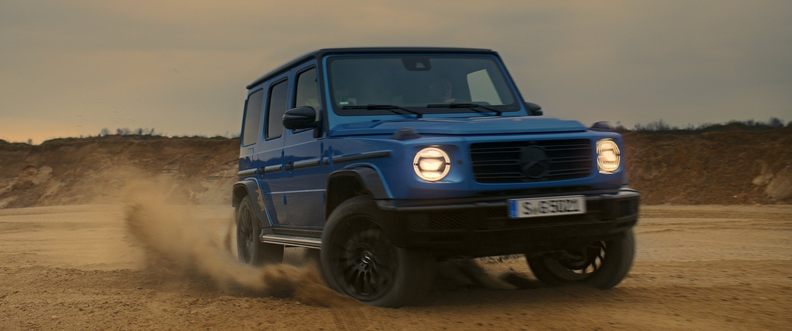The Mercedes-Benz G-Class drives through a desert.