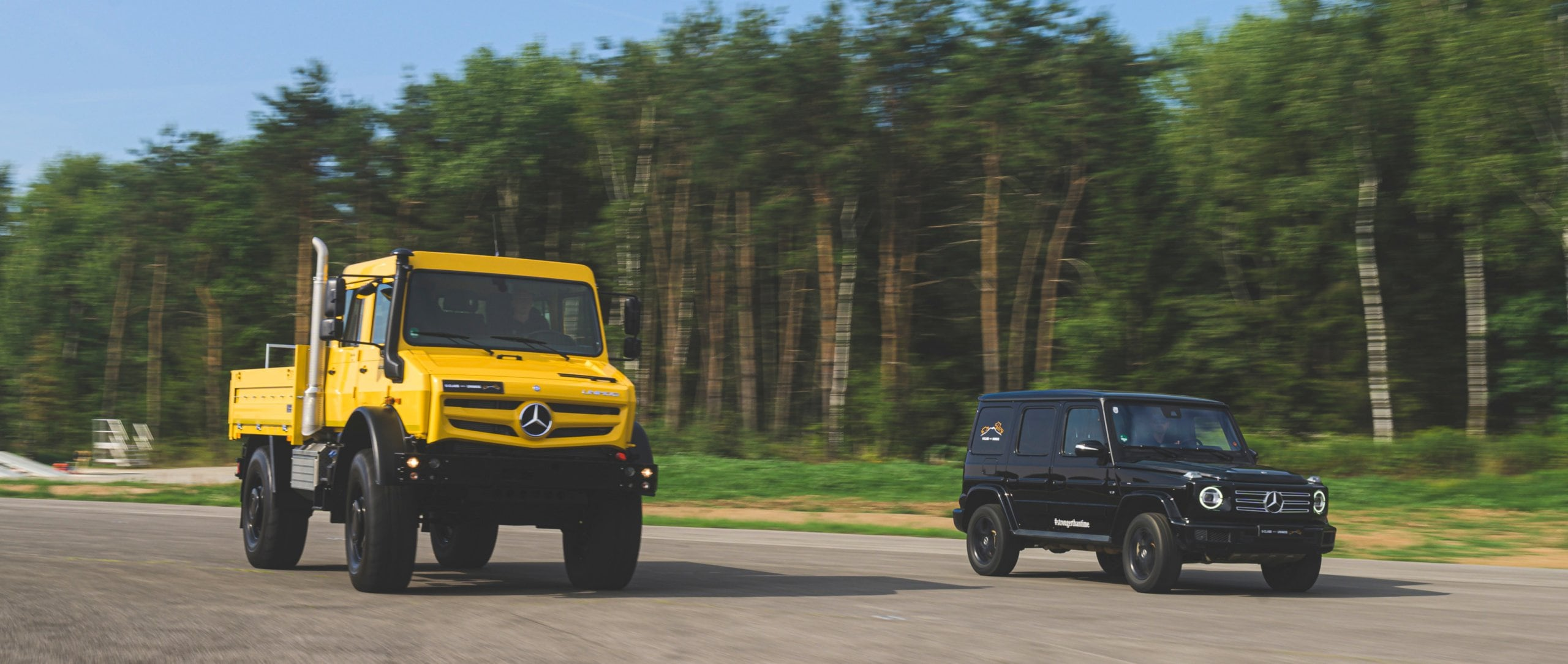 The Mercedes-Benz Unimog UHE 5023 in golden yellow and the Mercedes-Benz G-Class (W 463) in black.
