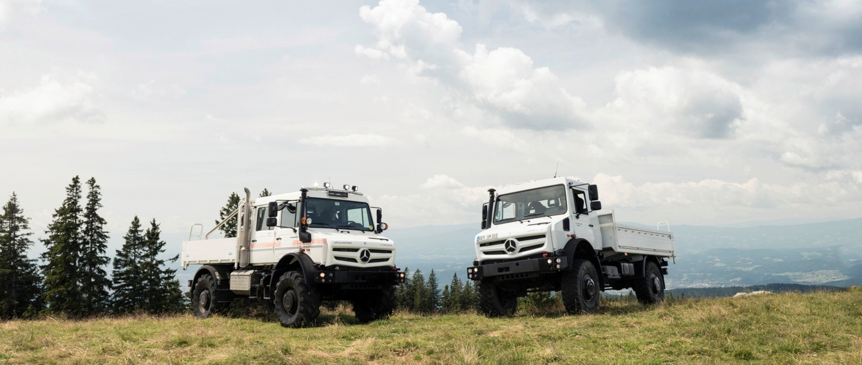 Two Mercedes-Benz Unimogs U 5023 in arctic white on a hill.