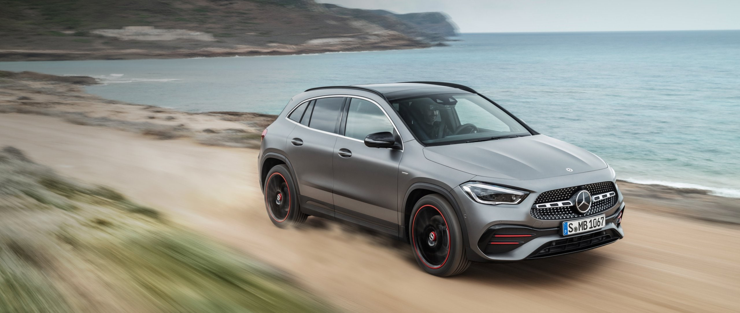 The new 2020 Mercedes-Benz GLA Edition1 AMG Line (H 247) in mountain grey magno driving along the coast.