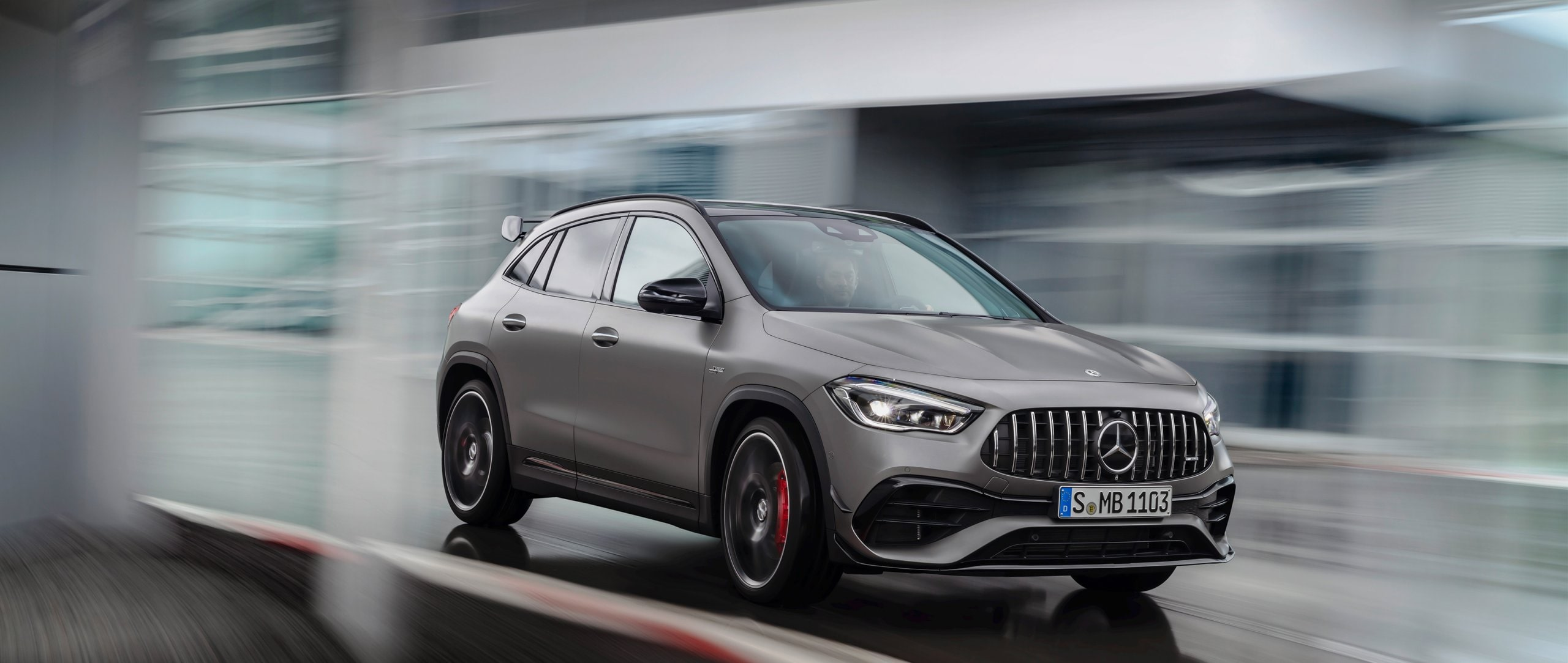 The new 2020 Mercedes-AMG GLA 45 4MATIC+ (H 247) in designo mountain grey magno on a racetrack