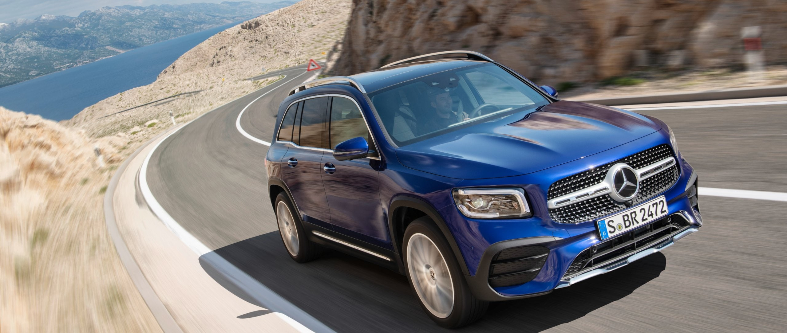 The new 2020 Mercedes-Benz GLB (X 247) in brilliant blue on a windy coastal road.