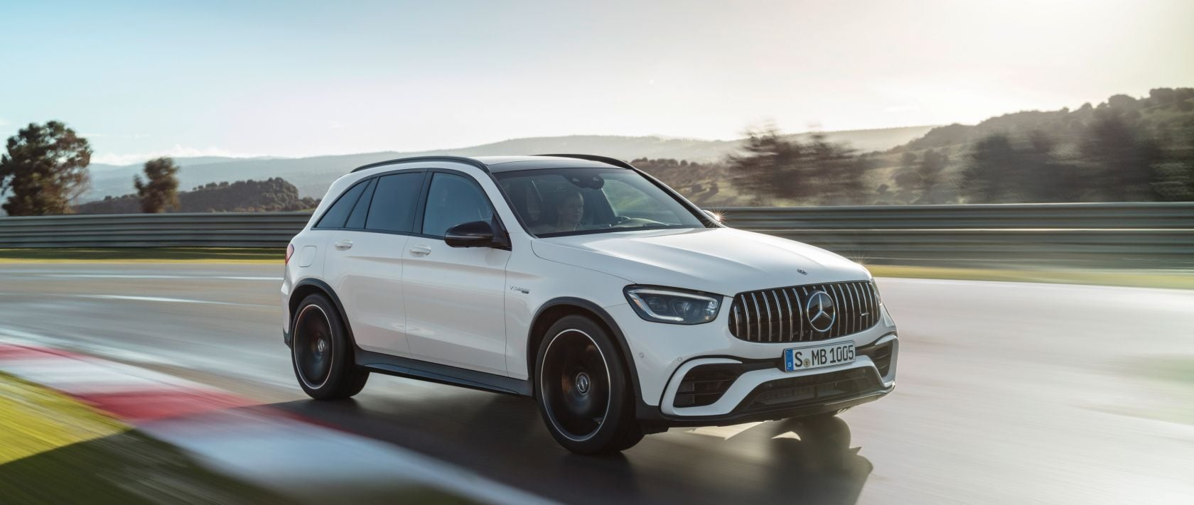 Front view of the new 2019 Mercedes-AMG GLC 63 S 4MATIC+ (X 253) in designo diamond white bright on a country road.