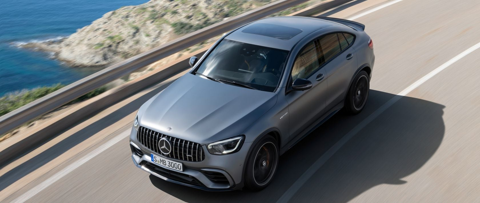 Bird's eye view of the new 2019 Mercedes-AMG GLC 63 S 4MATIC+ Coupé (C 253) in designo selenite grey magno on a country road.