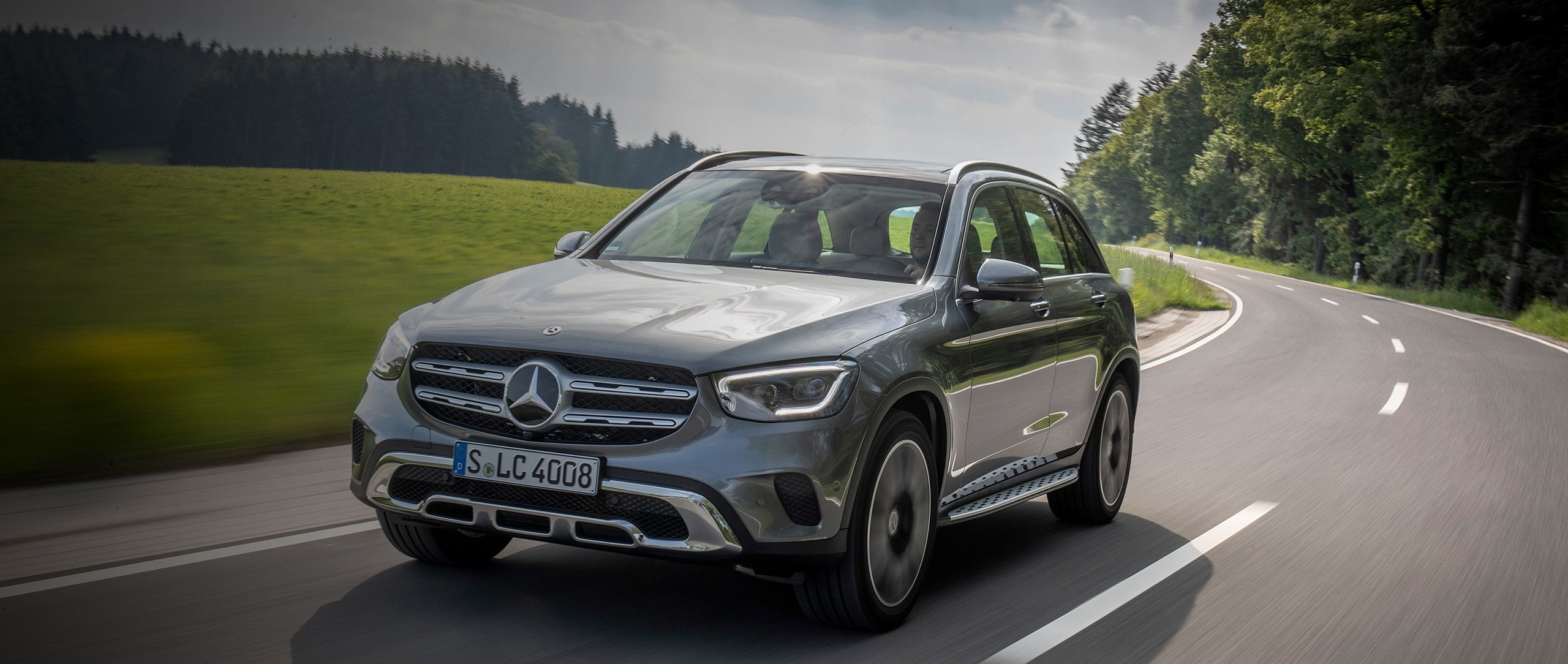 The Mercedes-Benz GLC driving on a country road.