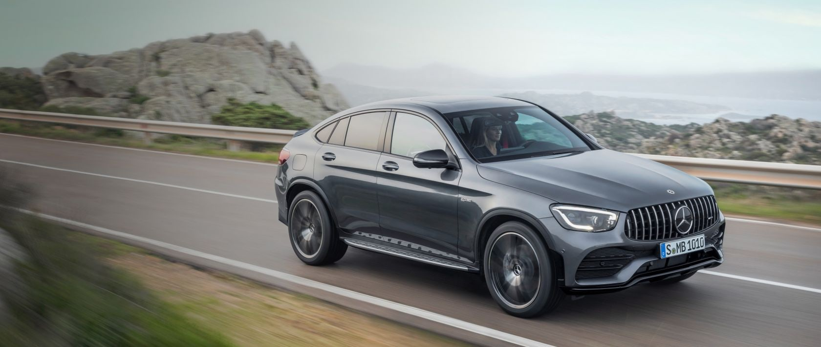 The 2019 Mercedes-AMG GLC 43 4MATIC Coupé (C 253) in selenite grey on a coastal road.