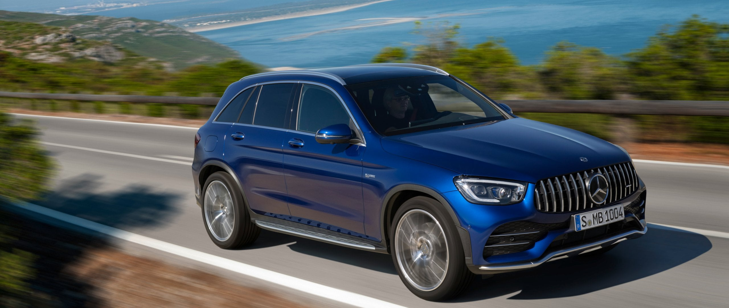 Front view: the 2019 Mercedes-AMG GLC 43 4MATIC SUV (X 253) in brilliant blue on a coastal road.